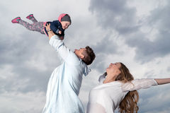 Young father throws up baby in the sky Stock Photos