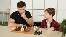 Young father is about to lose the chess game to his teenage son slow motion stock footage