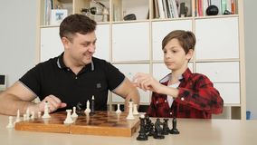 Young father tries to proove his son the rightness of the move of his chess fugure on the board slow motion stock video