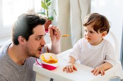 Father try to feeding a toddler boy with a spoon in a chair royalty free stock photos