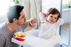 Father try to feeding a toddler boy with a spoon in a chair stock photo