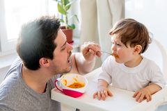 Father try to feeding a toddler boy with a spoon in a chair royalty free stock photography