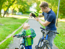 Young father trying to wear a bicycle helmet to his son stock photo