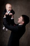 Young father in tuxedo holding his child Royalty Free Stock Image