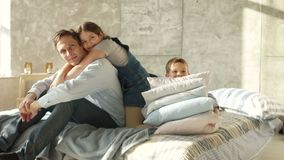 A young father with two children is sitting on the bed. Morning of a large family. Girl hugging father, boy playing with. Pillows stock video