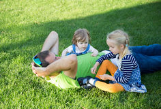 Young father with two daughters lying on grass in a park Stock Photos