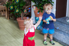 Young father and two little boys playing with soap bubbles in su. Two little brother boys playing with soap bubbles in summer outdoors Royalty Free Stock Images