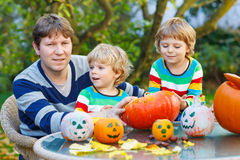 Young father and two little sons making jack-o-lantern for hallo. Young father and his two kid boys making jack-o-lantern for halloween in autumn garden Royalty Free Stock Image