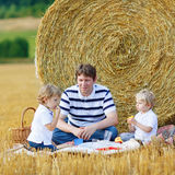 Young father and two little toddler boys having picnic on hay fi. Young father and two little toddler boys having picnic on yellow hay field in summer, outdoors Royalty Free Stock Images