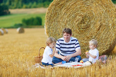 Young father and two little toddler boys having picnic on hay fi. Young father and two little toddler boys having picnic on yellow hay field in summer, outdoors Royalty Free Stock Image