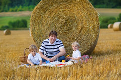 Young father and two little toddler boys picnicking on yellow hay field Stock Photo
