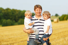 Young father and two little twins boys having fun on yellow hay Royalty Free Stock Photo