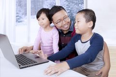 Young father using a laptop with his children. Photo of young father using a laptop with his children while studying together and sitting near the window stock images