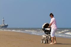 Young father walking with a baby stroller on a beach Royalty Free Stock Photo