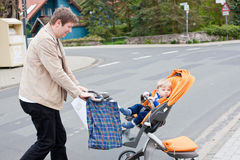 Young father walking with baby toddler in pram Royalty Free Stock Photography