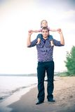 Young father walking dawn the river bank with his Stock Photography