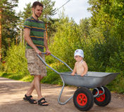 Young father walking with his little son. Son stands in garden wheelbarrow Stock Image