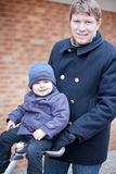 Young father walking with little toddler on pram Stock Photography