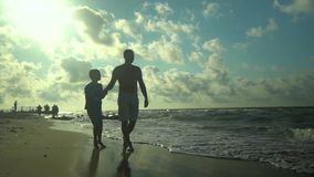 A young father walks with his son along the seashore. The sun shines brightly. They are talking. Family happiness. Trust