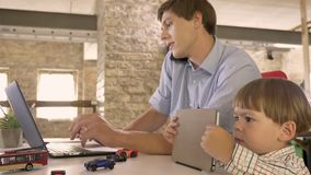 Young father working on laptop and talking on phone, little son watching tablet, busy and concentrated.  stock footage