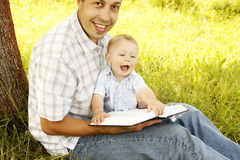 Young father with a young son reads the Bible Royalty Free Stock Photography