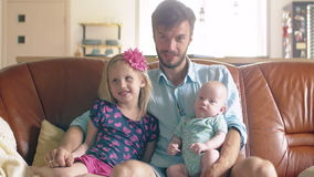Young fatheris sitting on the sofa with his newborn son and his daughter looking at the camera. 4k stock video footage