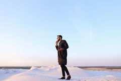 Muslim male tourist speaks on phone and shares news, standing in Stock Images