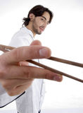 Young fellow in chef uniform holding chopsticks. On an isolated white background Stock Images