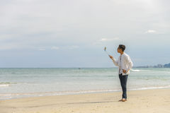 Young fellow using selfie stick in China Beach in Danang Stock Photos