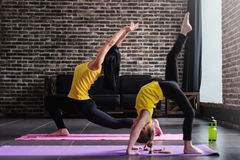 Young female adult doing crescent lunge pose and girl child standing in one-legged inverted staff position during yoga Royalty Free Stock Photography
