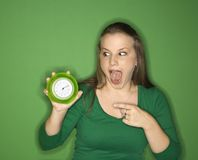 Young female adult pointing to clock. Stock Photo