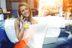 Young female with amazing smile speaking on cell telephone while sitting in front open laptop computer in modern interior Royalty Free Stock Photos