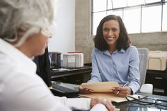 Young female analyst in consultation with senior woman royalty free stock photo