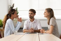 Young female applicant talking to diverse hr managers at office. Young female applicant talking to diverse hr managers sitting at office desk. Male executive royalty free stock photography