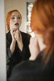Young female applying lip liner in front of mirror Stock Photos