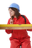 Young female apprentice in red overall. Young female apprentice wit yellow level in red overall isolated on white background royalty free stock photo