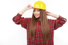 Young female architect or builder wearing a yellow hart hat on a Stock Photo