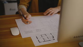 Young female architect drawing line on blueprint stock video