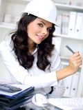 Young female architect or engineer. Attractive young female architect or engineer wearing a white hardhat sitting in her office working and looking at the camera Stock Photos
