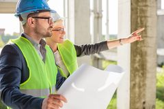 Young female architect pointing at something to her colleague at a construction site royalty free stock photos