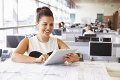 Young female architect using tablet computer at her desk Stock Image