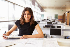 Young female architect working with computer and blueprints Royalty Free Stock Photo