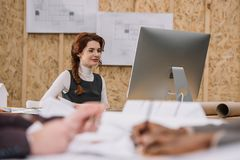 young female architect working with computer at office while colleagues drawong plans Royalty Free Stock Image