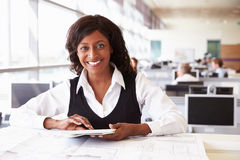 Young female architect working at desk, looking to camera royalty free stock image