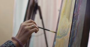 Young Female Artist is in an Art Studio, Sitting Behind an Easel and Painting on Canvas. Drawing Process: in the Art. A Young Beautiful Female Artist is in an stock video footage