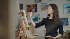 Woman painter working in studio. Young female artist concentrated with her painting. She working on easel in studio stock video footage
