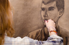 Young female artist drawing man portrait. In her art studio stock photography