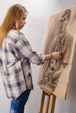 Young female artist drawing man portrait art studio. Young female artist drawing man portrait in her art studio stock photo