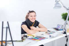 Young female artist drawing sketch using sketchbook with pencil at her workplace in studio. Side view portrait of Stock Image