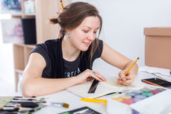 Young female artist drawing sketch using sketchbook with pencil at her workplace in studio. Side view portrait of Stock Photo